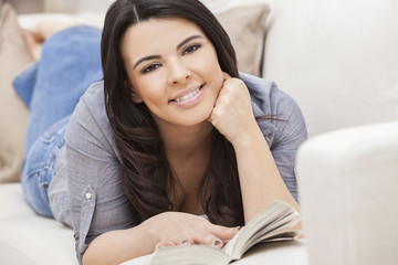 Happy Hispanic Woman Reading Paperback Book at Home