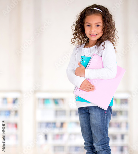 Little girl holding notebooks