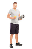 Male holding a glass of juice and a mat after an excerise