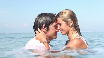 Pretty woman swimming in ocean then kissing her boyfriend