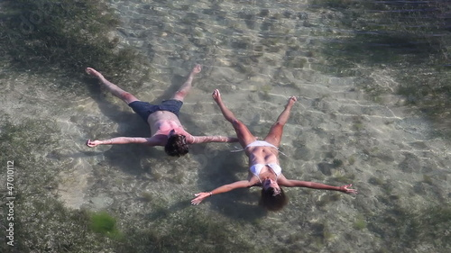 Couple stretching their hands and legs enjoying in ocean