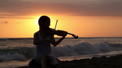 Silhouette of woman playing romantic music on violin on shore