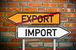 Wegweiser vor Ziegelsteinwand mit Export und Import