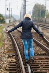 Frau balanciert auf Gleis. Entscheidungen
