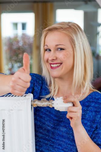 Frau senkt die Raumtemperatur
