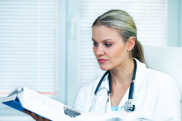 Pretty Young Female Doctor Is Studying from a Medical Book in He