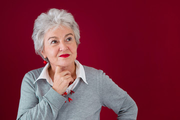 Nachdenkliche ältere Dame mit rotem Hintergrund