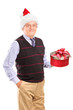 Smiling mature gentleman with christmas hat holding gift in his