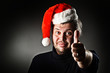 Sa Kind smiling man wearing Santa hat with thumb up.