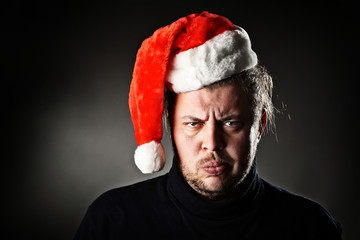 Portrait of angry man wearing santa hat against dark background.