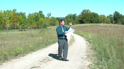 Businessman Lost with Map on Dirt Road