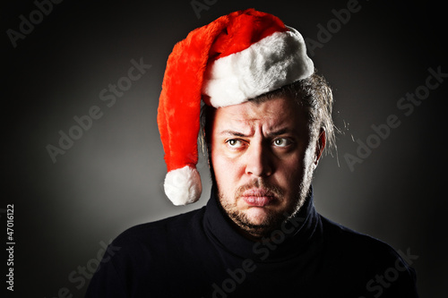 Portrait of upset man wearing santa hat against dark background.