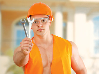 Young construction worker posing with spanner outdoors