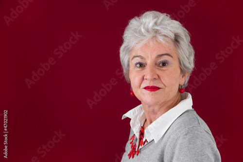 Ernste ältere Frau in Rot und Grau