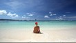 Woman in Santa Claus hat sitting on tropical beach