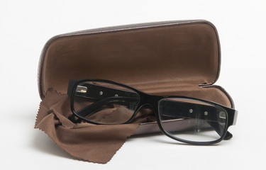 Points in a black frame, a brown case and a napkin for optics on