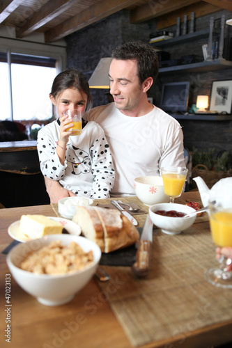 Man and little girl having breakfast
