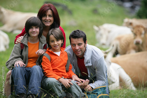Young family sitting in a field of cattle