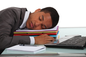 Businessman asleep on pile of folders