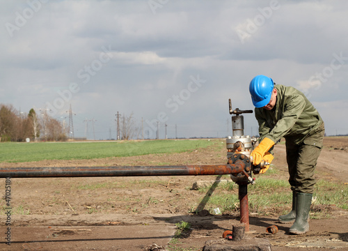 oil worker closes the valve