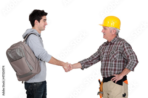 Builder shaking apprentice's hand