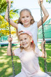 two girls  on the playground on a  swing