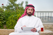 Arabian man relaxing in garden and working online on the pad
