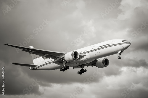sepia toned unmarked passenger aircraft landing