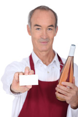 Waiter holding bottle of wine and blank business card