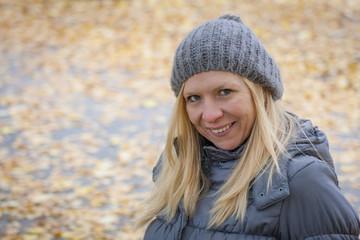 Blonde Frau vor Herbsthintergrund