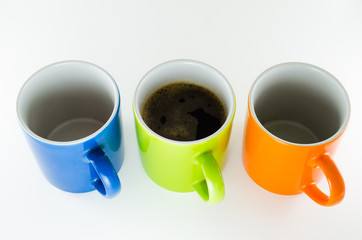 Três canecas em linha reta com café na caneca do centro.