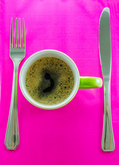 Caneca verde com café em pires com talheres.