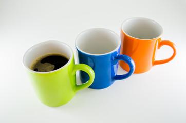 Três canecas na diagonal com café na primeira caneca