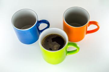 Três canecas, sendo uma verde com café.