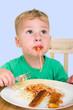 Junge isst Nudeln mit Tomatensoße und Fischstäbchen