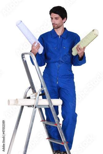 Man stood on step-ladder choosing which color wallpaper to use
