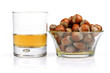 a glass of whiskey and a bowl of nuts