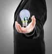 Business man holding  light bulb with  wind turbine and earth in