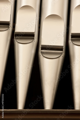 A close-up detail of silver organ pipes.