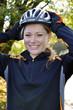 Junge Frau setzt Fahrradhelm auf