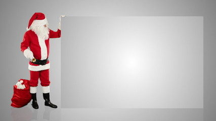 Santa Claus shaking bell presenting a white sheet