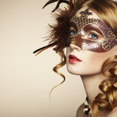 Beautiful young woman in brown mysterious venetian mask