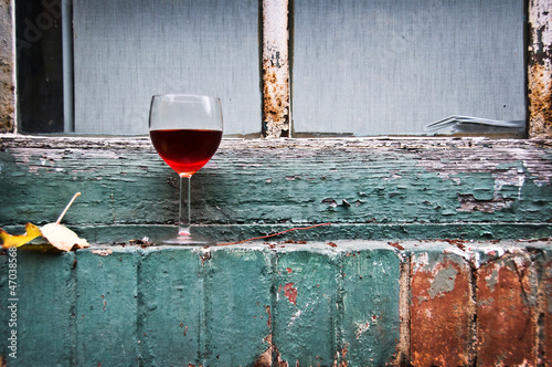 Verre de vin rouge sur un bord de fenêtre - 47038568