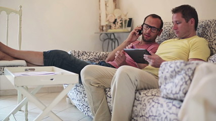 Gay couple with tablet computer and cellphone on sofa