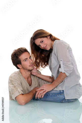 Young couple sat on glass desk
