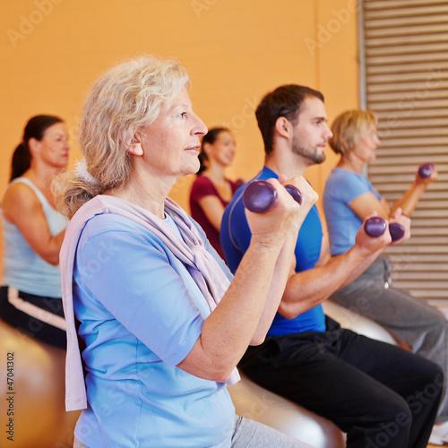 Seniorin beim Hanteltraining im Fitnesscenter