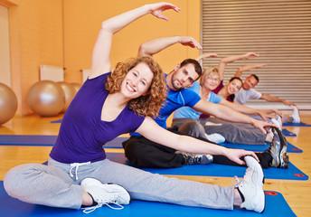 Gruppe macht Dehnübungen im Sportstudio