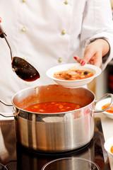 chef cooking solyanka in kitchen