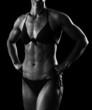 Muscular female body against black background.