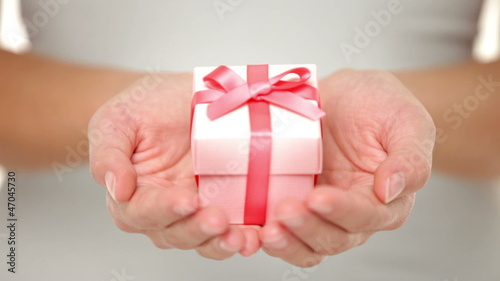 Gift closeup. Red present of gift in closeup in woman hand.